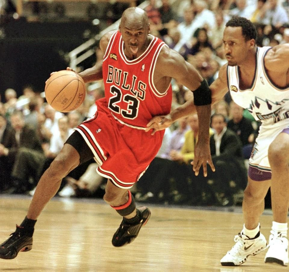Michael Jordan best in NBA history with red Bulls jersey driving into the paint with tongue out.