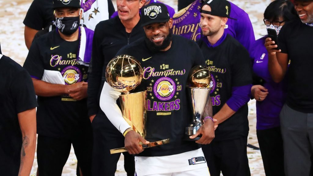 LeBron James, the GOAT, holding Finals MVP and Larry O'Brien trophies.